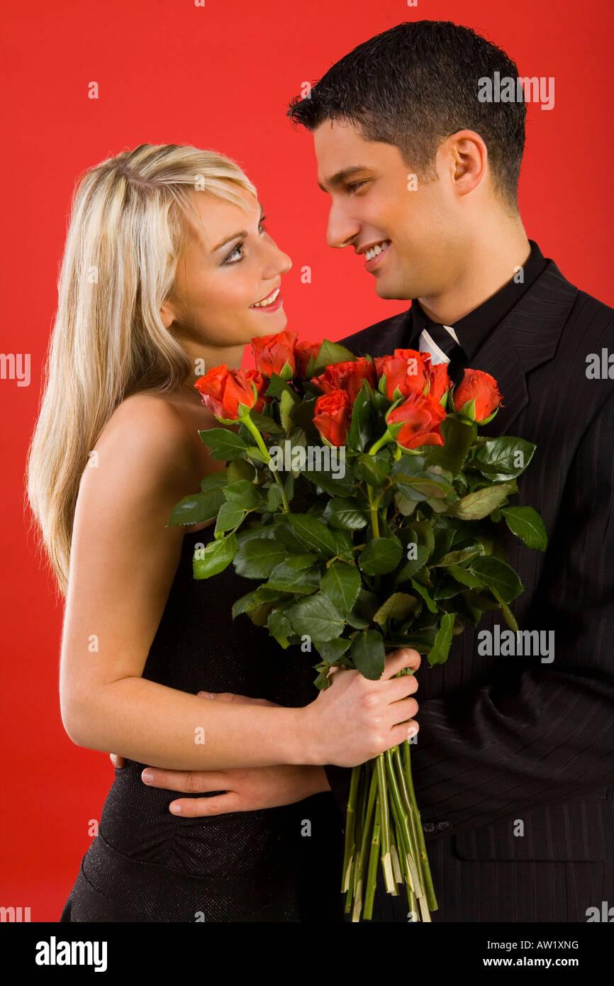 Junges Paar in glücklichen Umarmung Womanan hält Rosenstrauß lächelnd und Mann Seitenansicht Stockbild