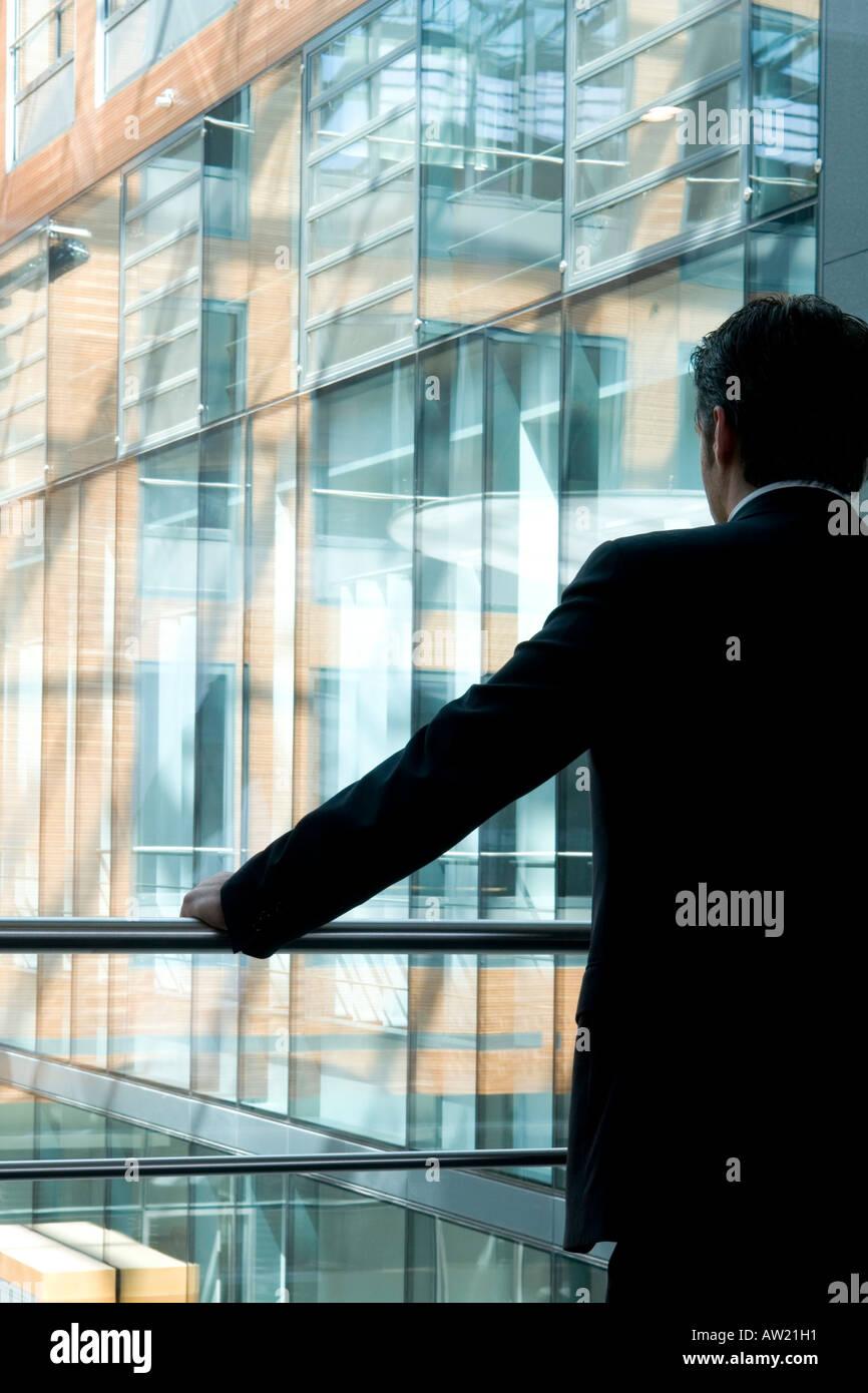 Mann am Fenster in einem Bürogebäude Stockfoto