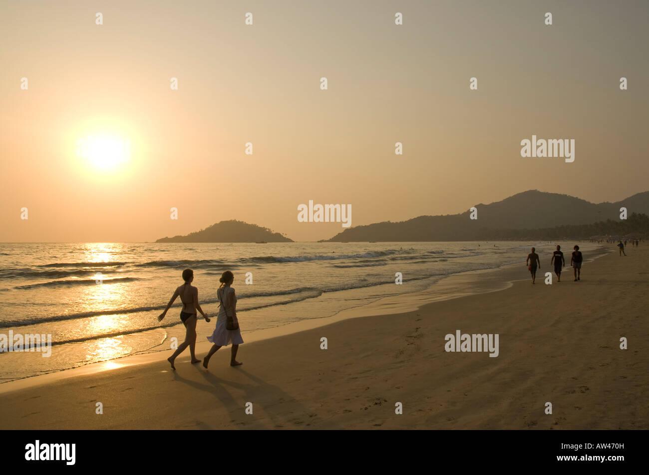 Menschen zu Fuß entlang Palolem Beach in Goa in Südindien bei Sonnenuntergang Stockbild