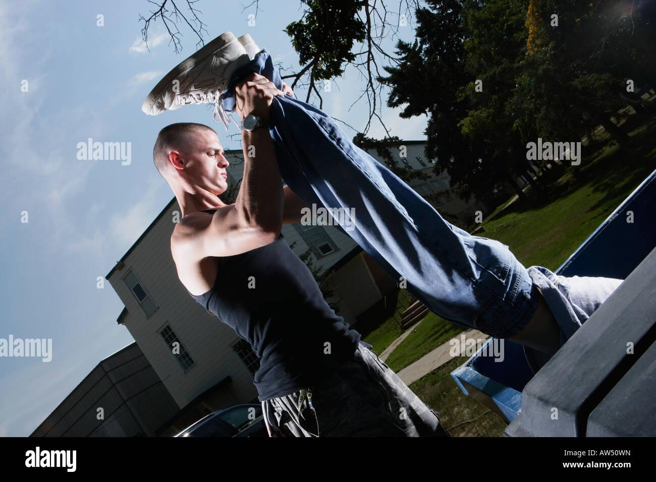 Mann hält eine Person an den Beinen Stockfoto