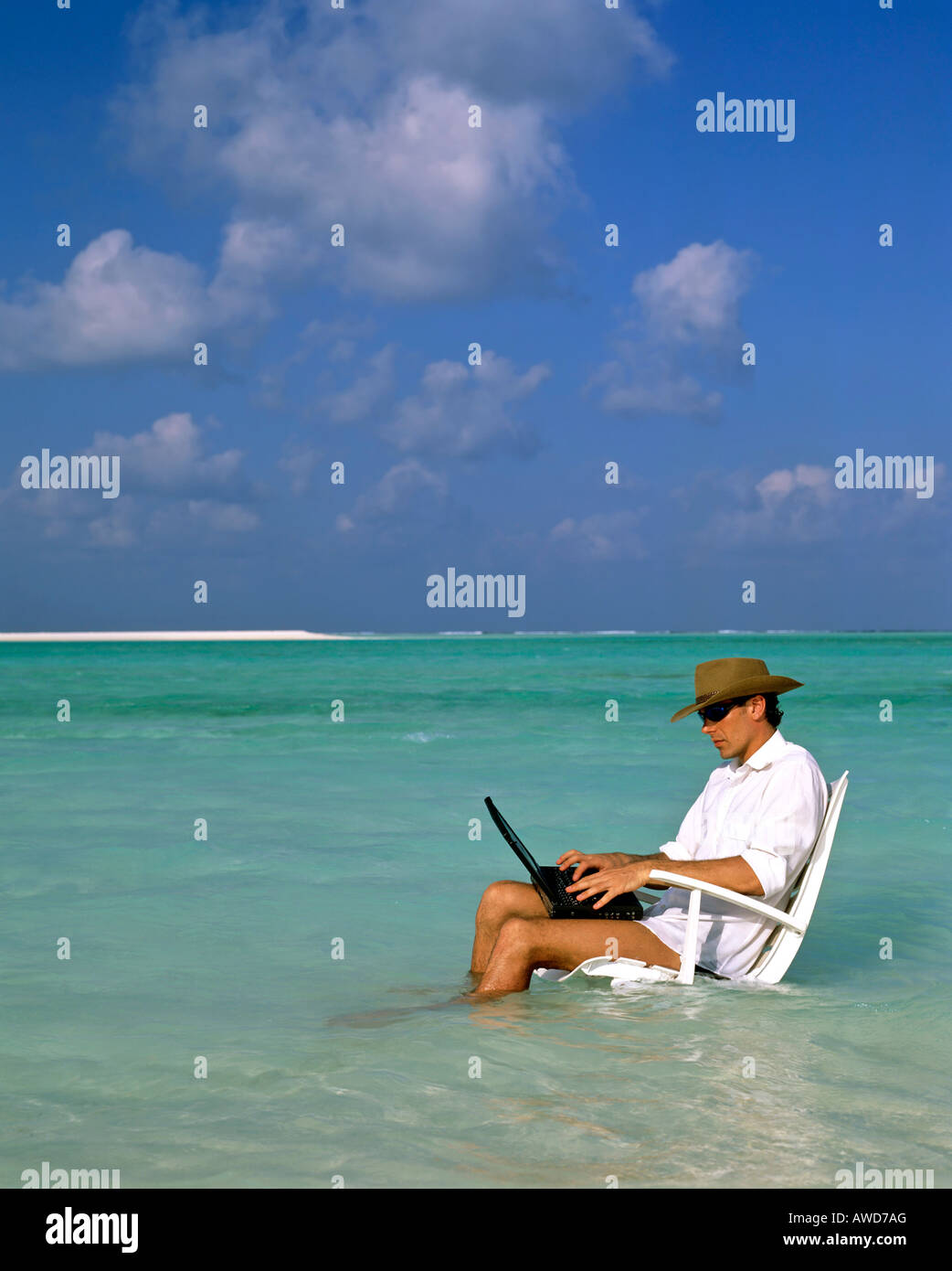Junger Mann mit Laptop sitzen im Liegestuhl, Arbeit und Entspannung, Urlaub und Stress, Malediven, Indischer Ozean Stockfoto