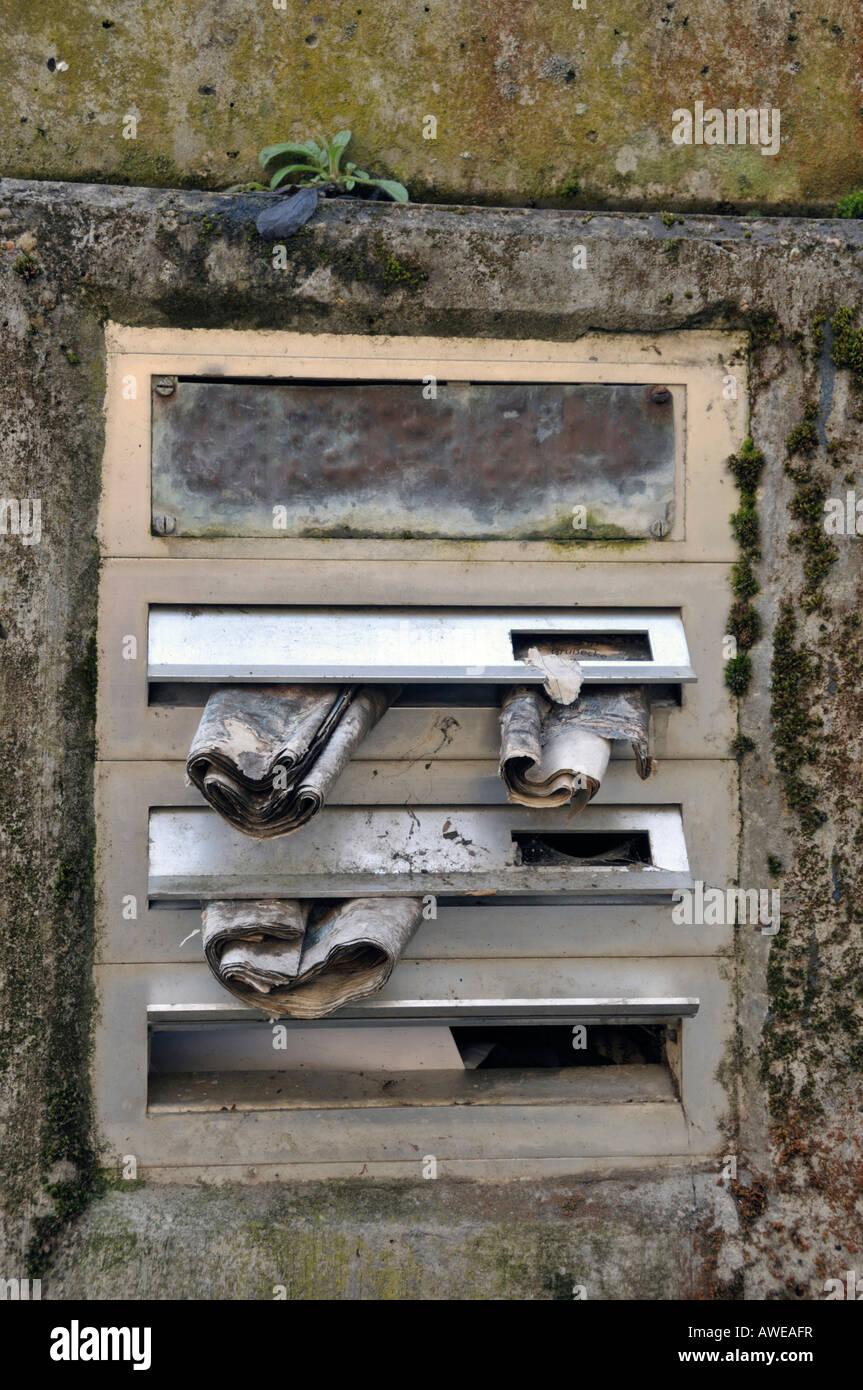 Briefkasten mit alten Zeitungen Stockbild