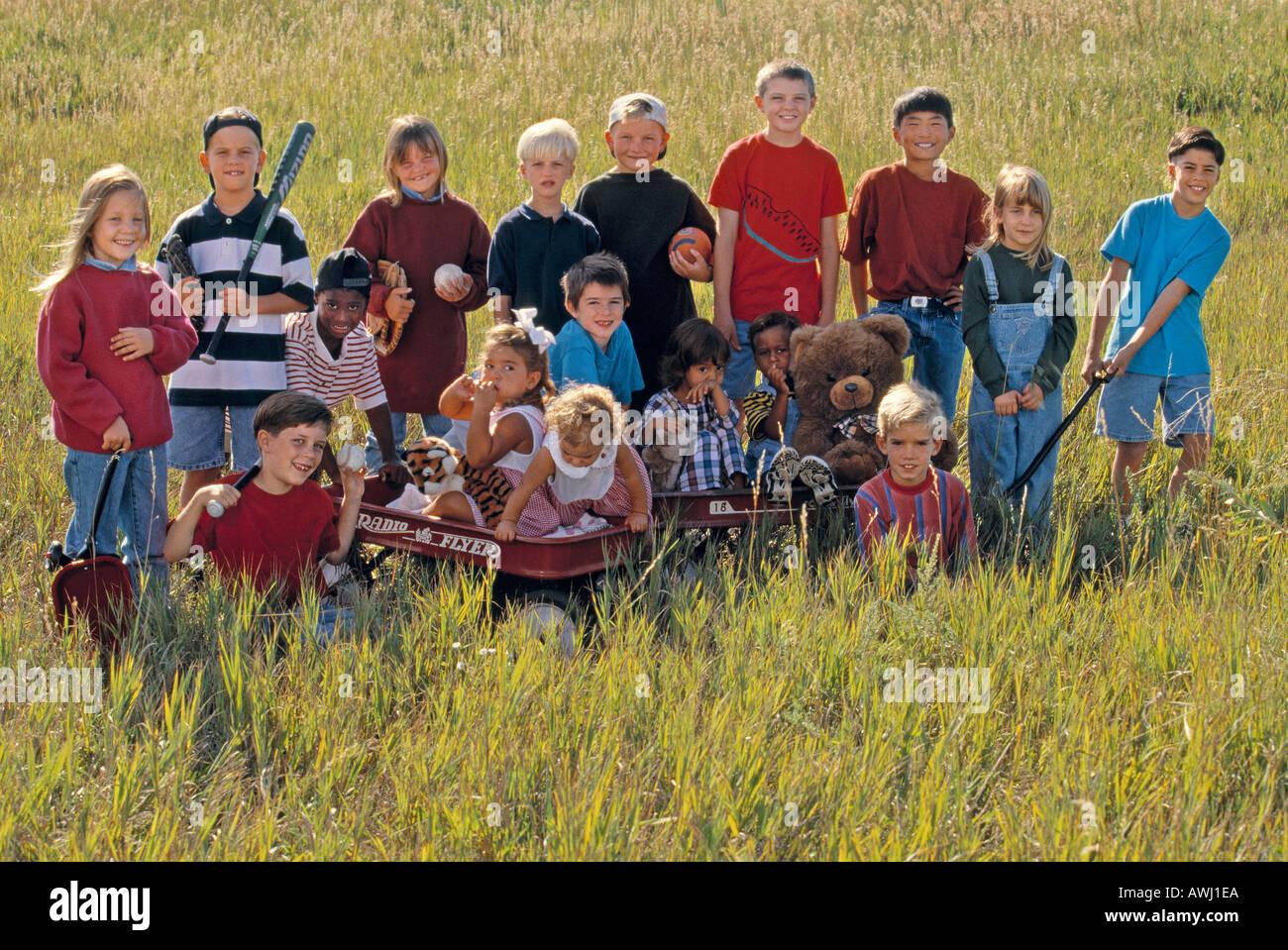 Eine Gruppe von multiethnischen Kinder mit Spielzeug und Wagen in einem Feld Gras Stockbild