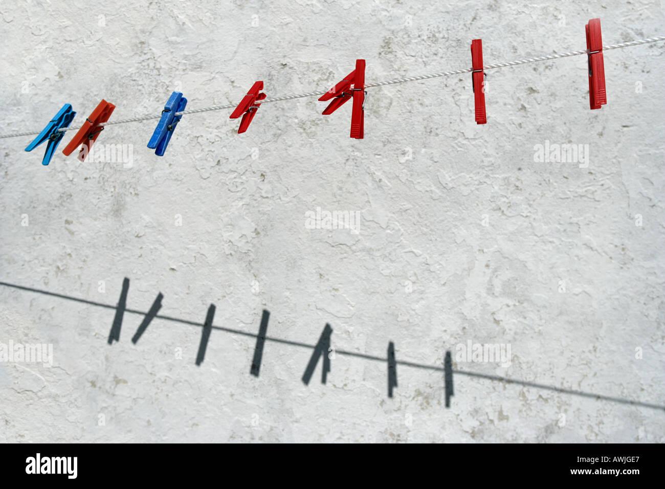 Farbige Kunststoff-Wäscheklammern von einer Wäscheleine hängen Stockbild