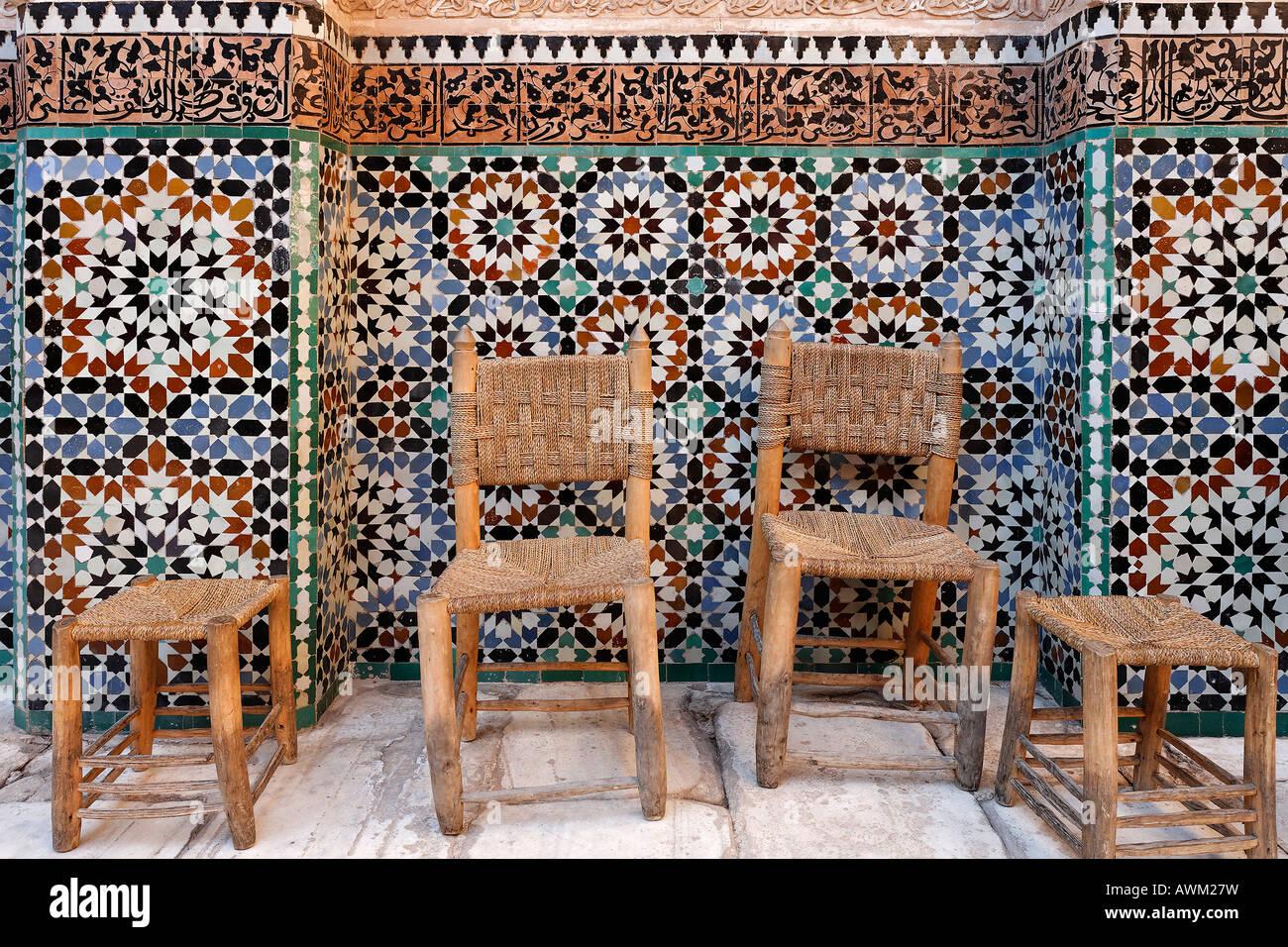 Alte hölzerne Stühle und Hocker vor einem wunderschönen Fliesen ...