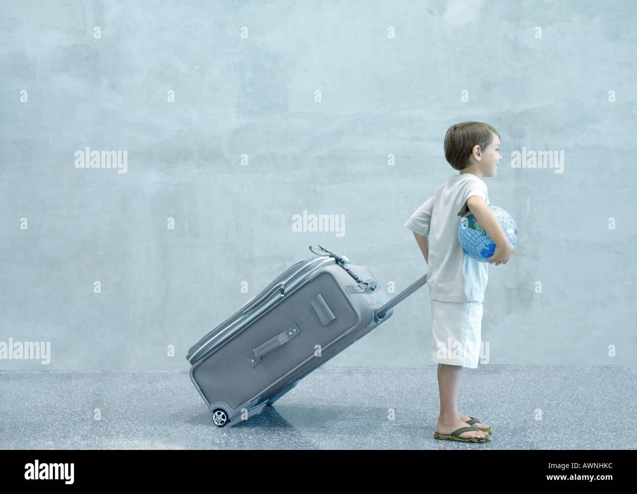 Junge mit Koffer und Globus Stockbild