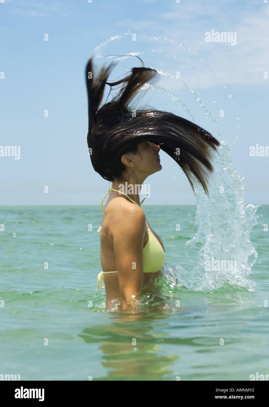Frau im Meer stehen, wirft Haar Stockbild