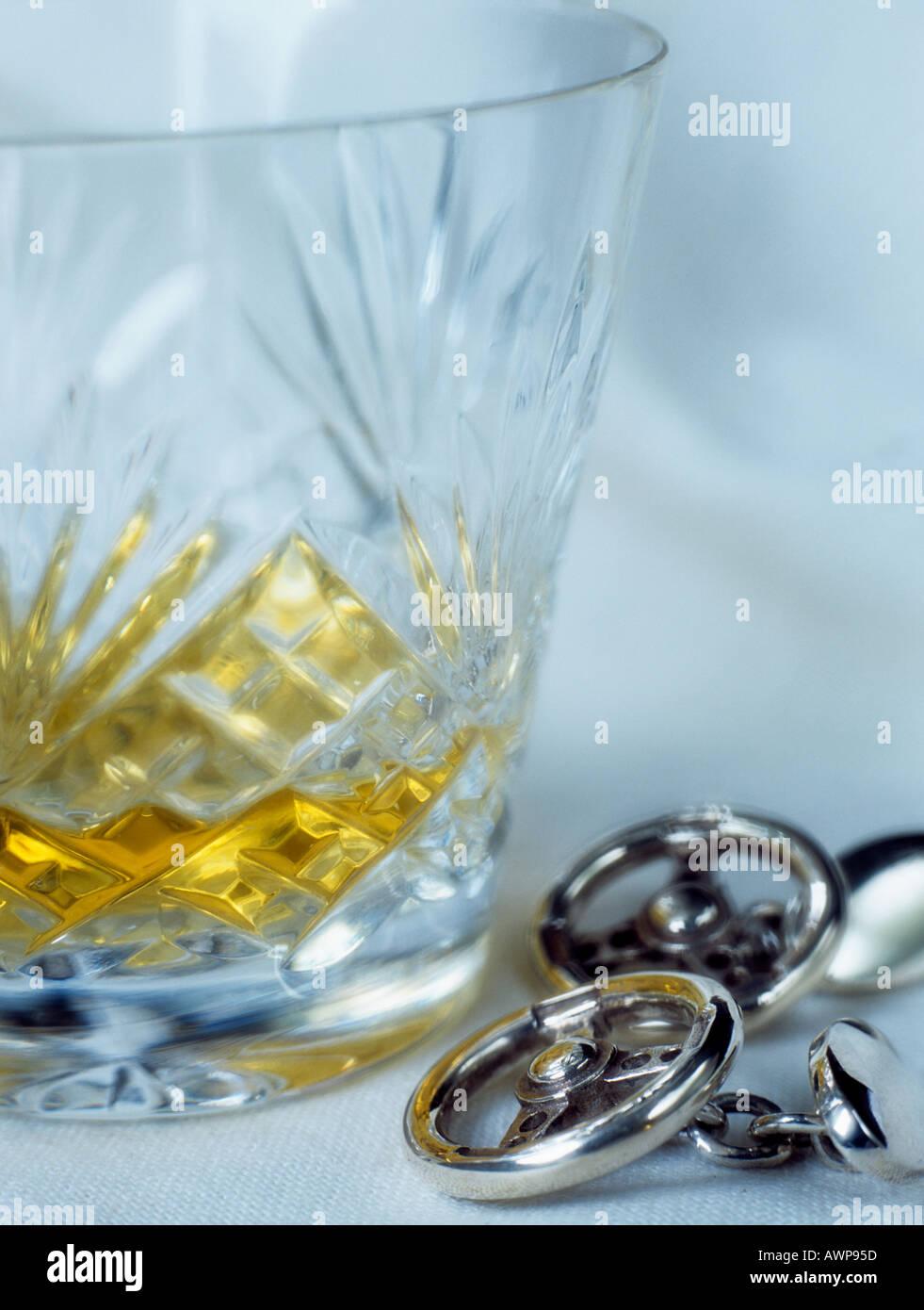 Ein Schuss von single Malt Whisky in einem Kristall Schnitt Whisky Glas Tumbler neben Herren Lenkrad Manschettenknöpfe illustrieren nicht trinken Antriebskonzept. UK Stockbild
