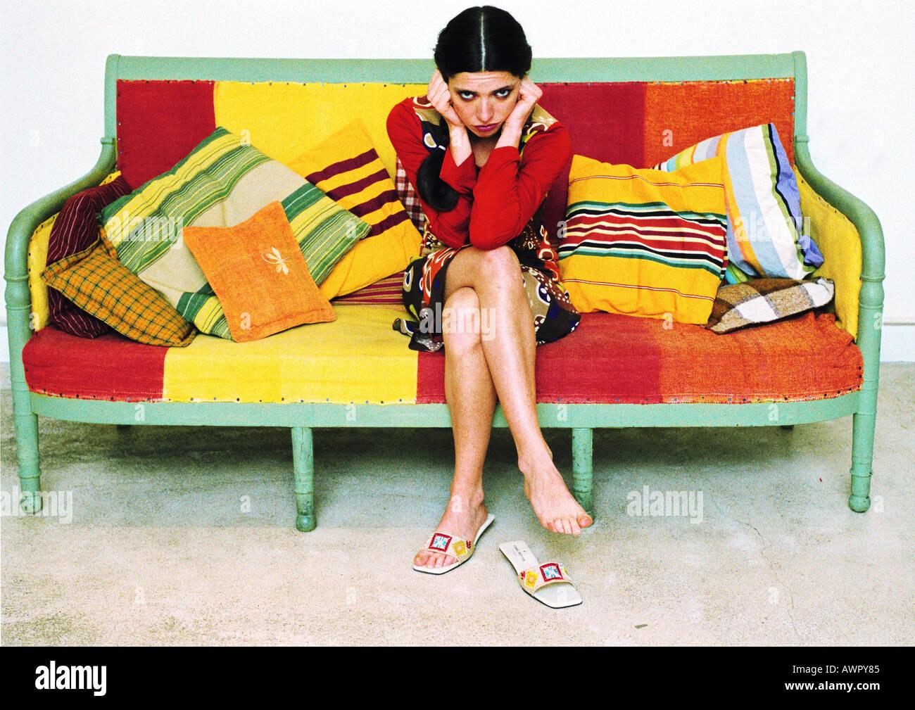 Junge Frau sitzt auf dem Sofa in Kamera. Stockfoto