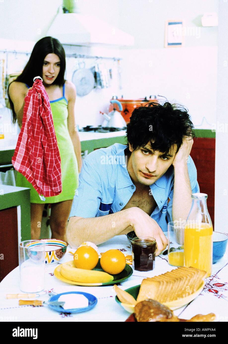 Mann sitzt am Frühstückstisch, Frau hinter dem Mann, mit Küchentuch. Stockfoto