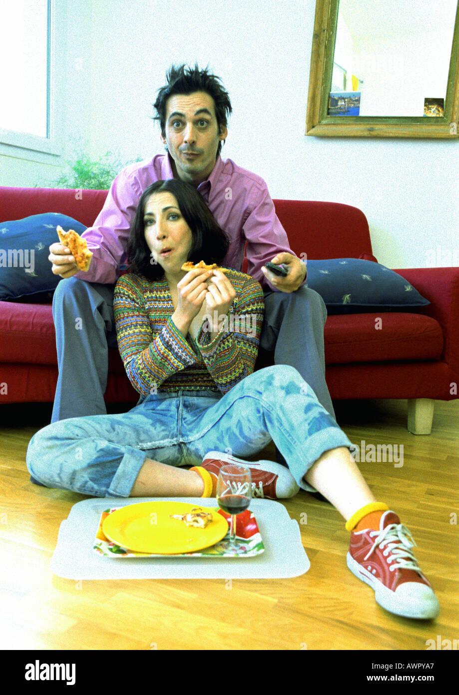 Mann sitzt auf dem Sofa, Frau sitzt am Boden zwischen den Beinen des Mannes. Stockfoto