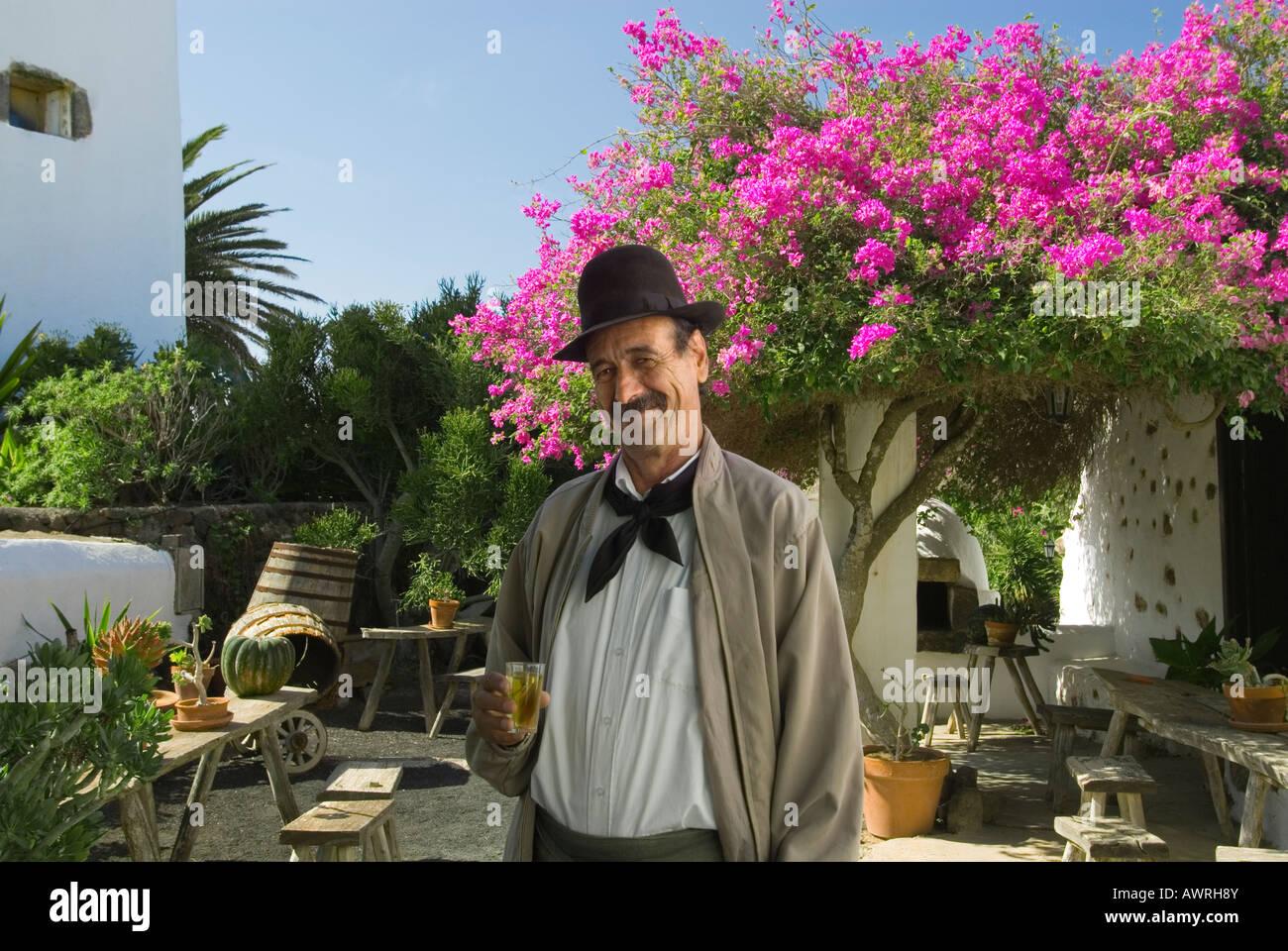 Winzer außerhalb seiner typischen sonnigen Bodega mit einem Glas Lanzarote weißen Malvasia Wein, Lanzarote Stockbild