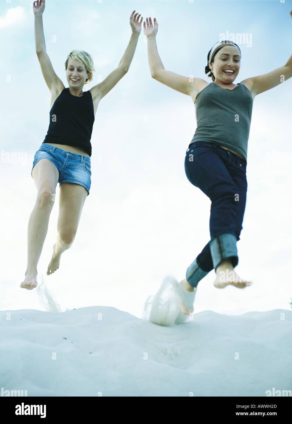 Frauen springen auf Sand, niedrigen Winkel Ansicht Stockbild