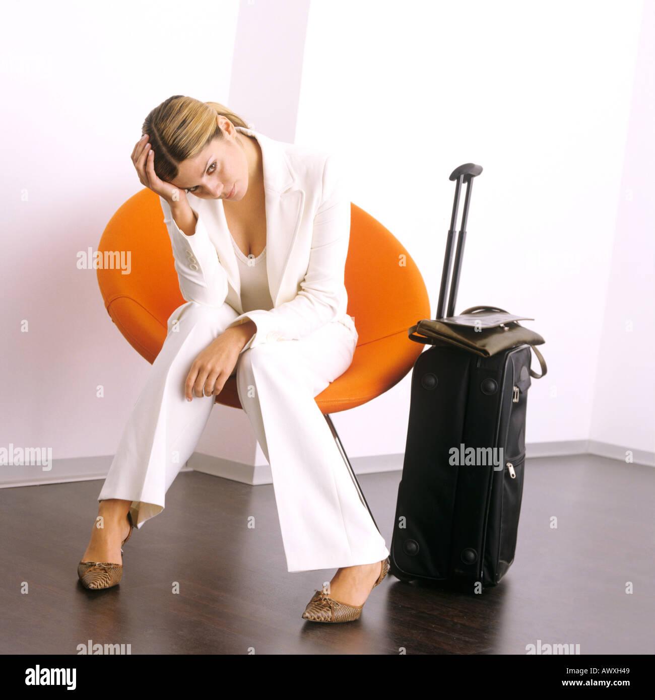 junge Geschäftsfrau warten im Liegestuhl mit Gepäck suchen gelangweilt und frustriert Stockfoto