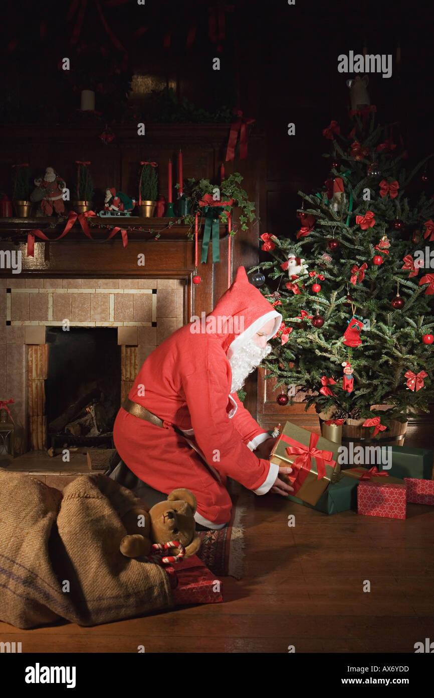 Weihnachtsmann, die Geschenke unter dem Weihnachtsbaum platzieren Stockbild