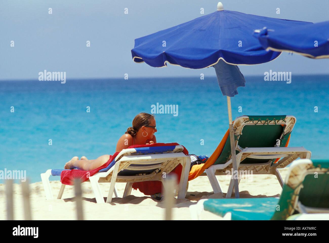 Liegestuhl mit sonnenschirm strand  Frau liegend im Liegestuhl unter dem Sonnenschirm, Strand von ...