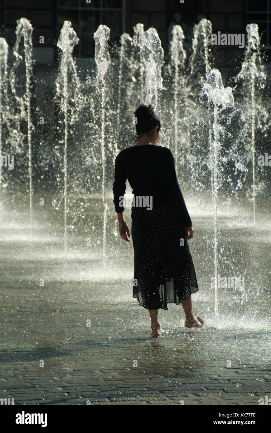Springbrunnen Wasserspiel junge Frau Abkühlung heißes Sommerwetter Konzept das Wasser oder tauchen Zehe im Wasser London England Großbritannien Stockbild