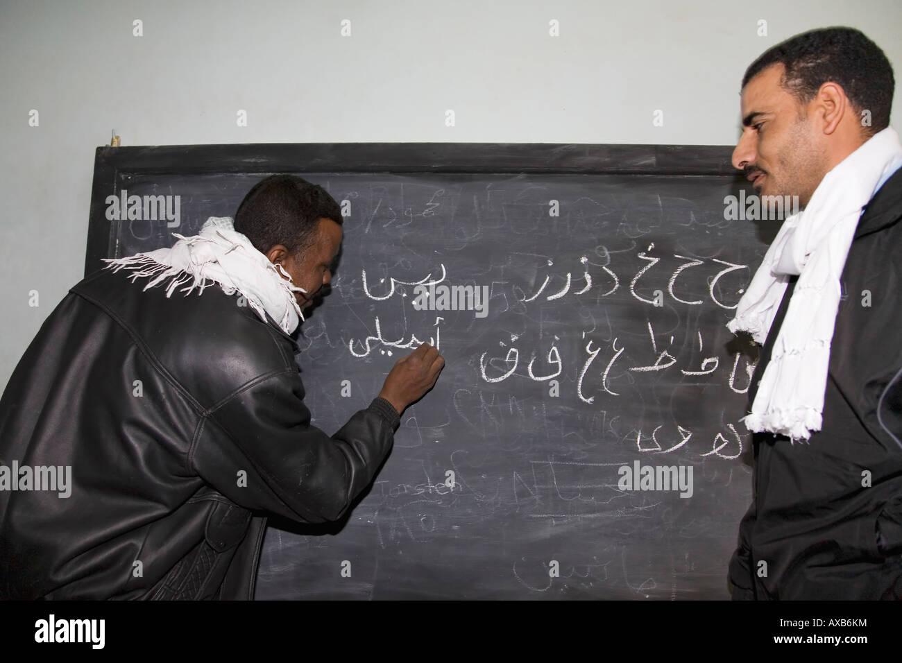 Ägyptische Lehrer unterrichten arabische Schrift auf Tafel im Klassenzimmer im nubischen Dorf in der Nähe Stockbild