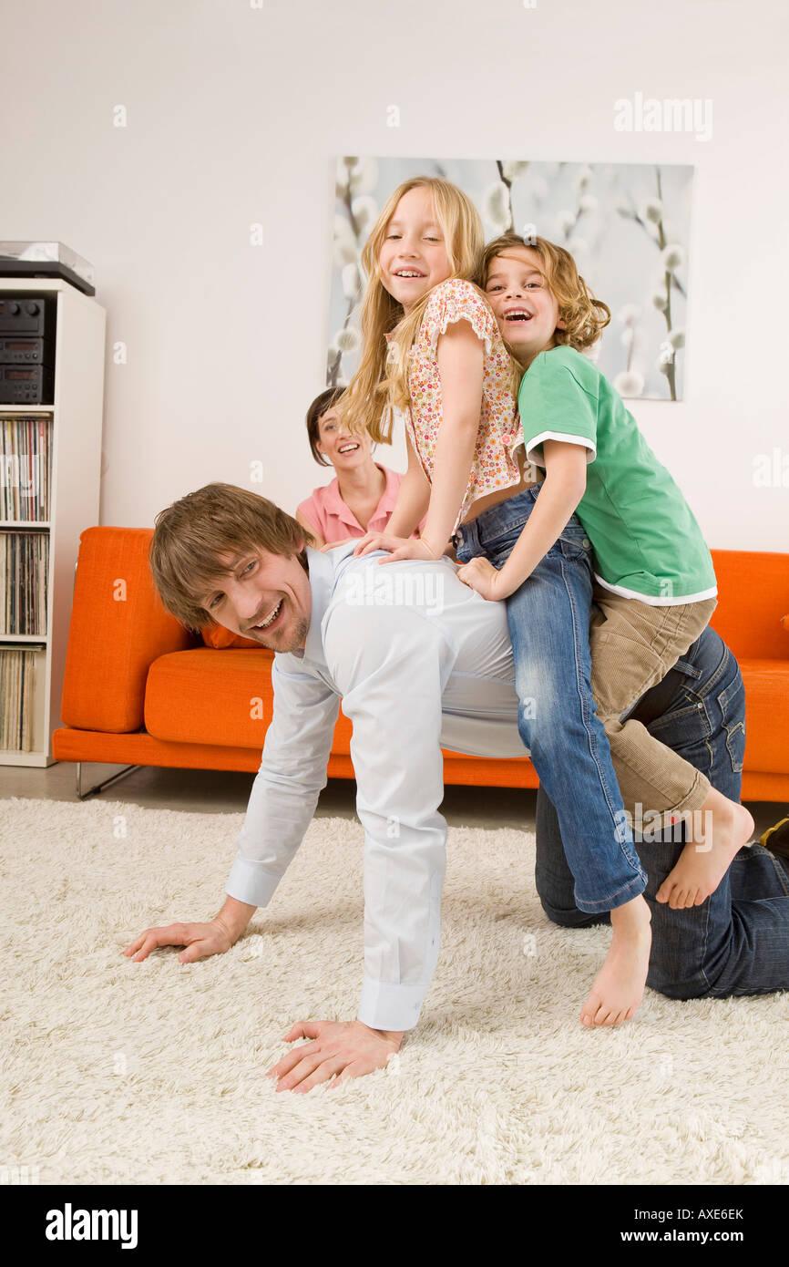 (6-7) jungen und Mädchen ist (8-9) auf Vater zurück im Wohnzimmer Stockfoto
