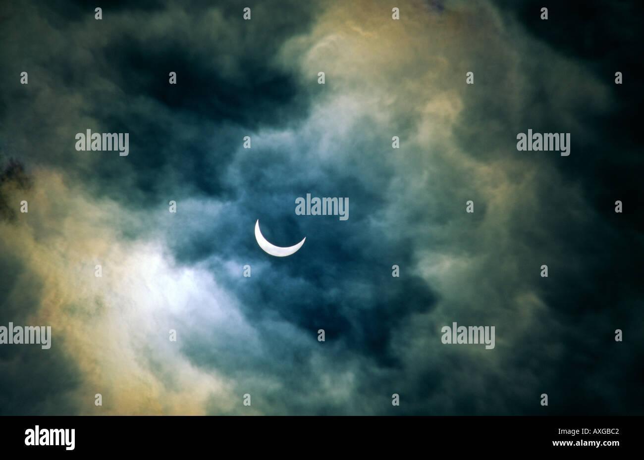 Sonnenfinsternis. Mond Sonne nähert sich volle Sonnenfinsternis vorbei.  Romantische Atmosphäre, die durch dünne stürmischen Clearing Wolke verschleiert Stockbild