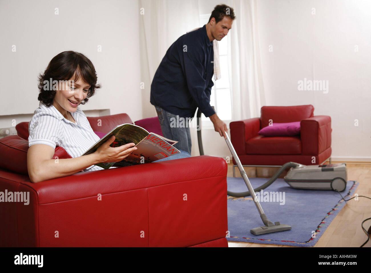 Symbole der Partnerschaft er saugt den Teppich, während sie eine Zeitschrift liest Stockfoto
