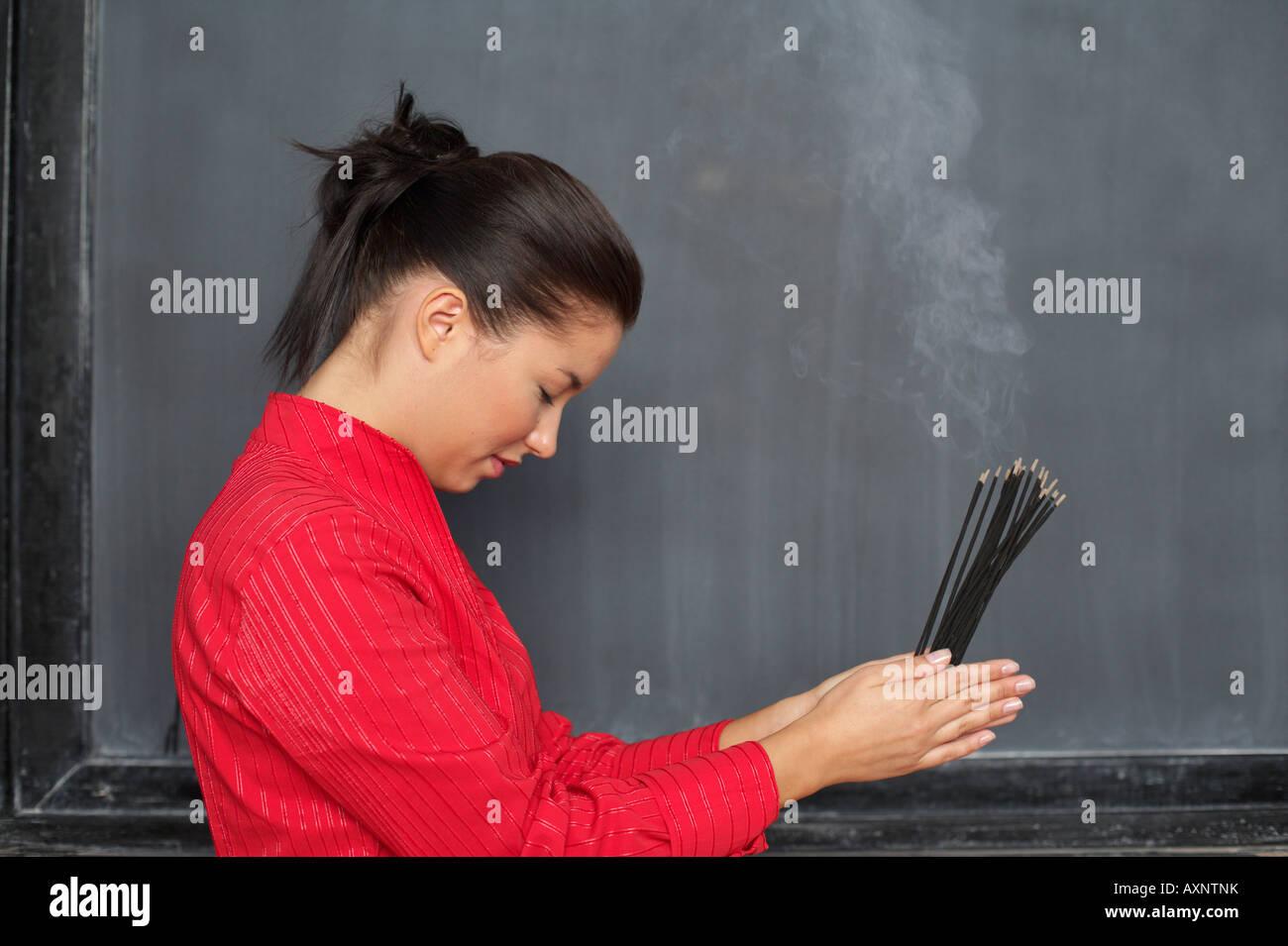 Asiatische Frau hält Stäbchen vor einer Tafel Stockbild