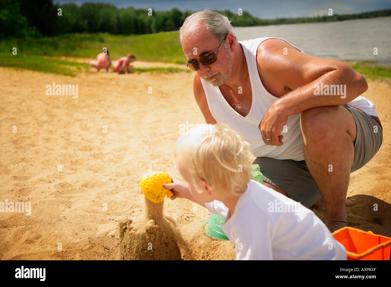 Großvater wacht über Enkelkind am Strand Stockfoto