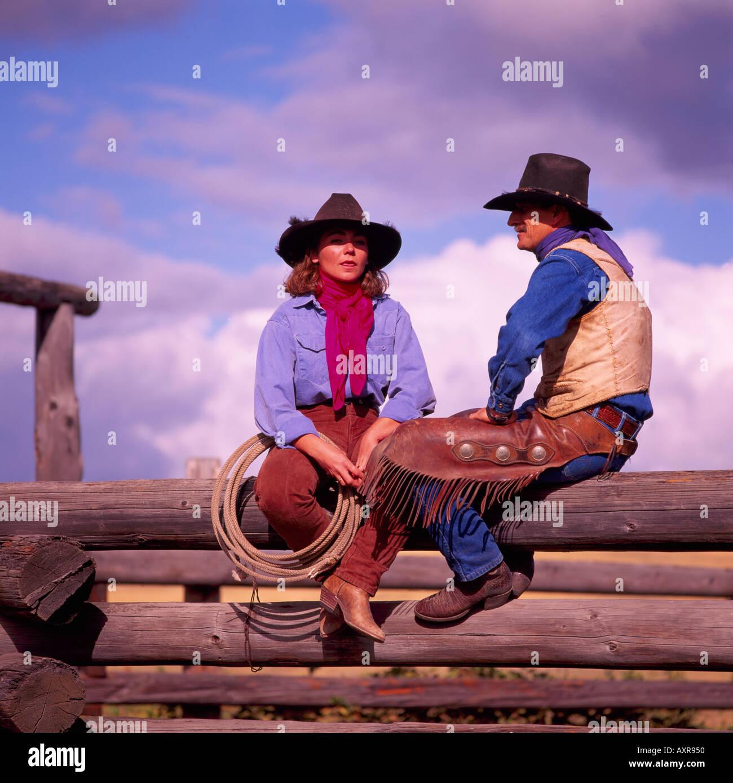 Cowgirl und Cowboy sitzt auf einem Holzzaun Log Corral Stockfoto