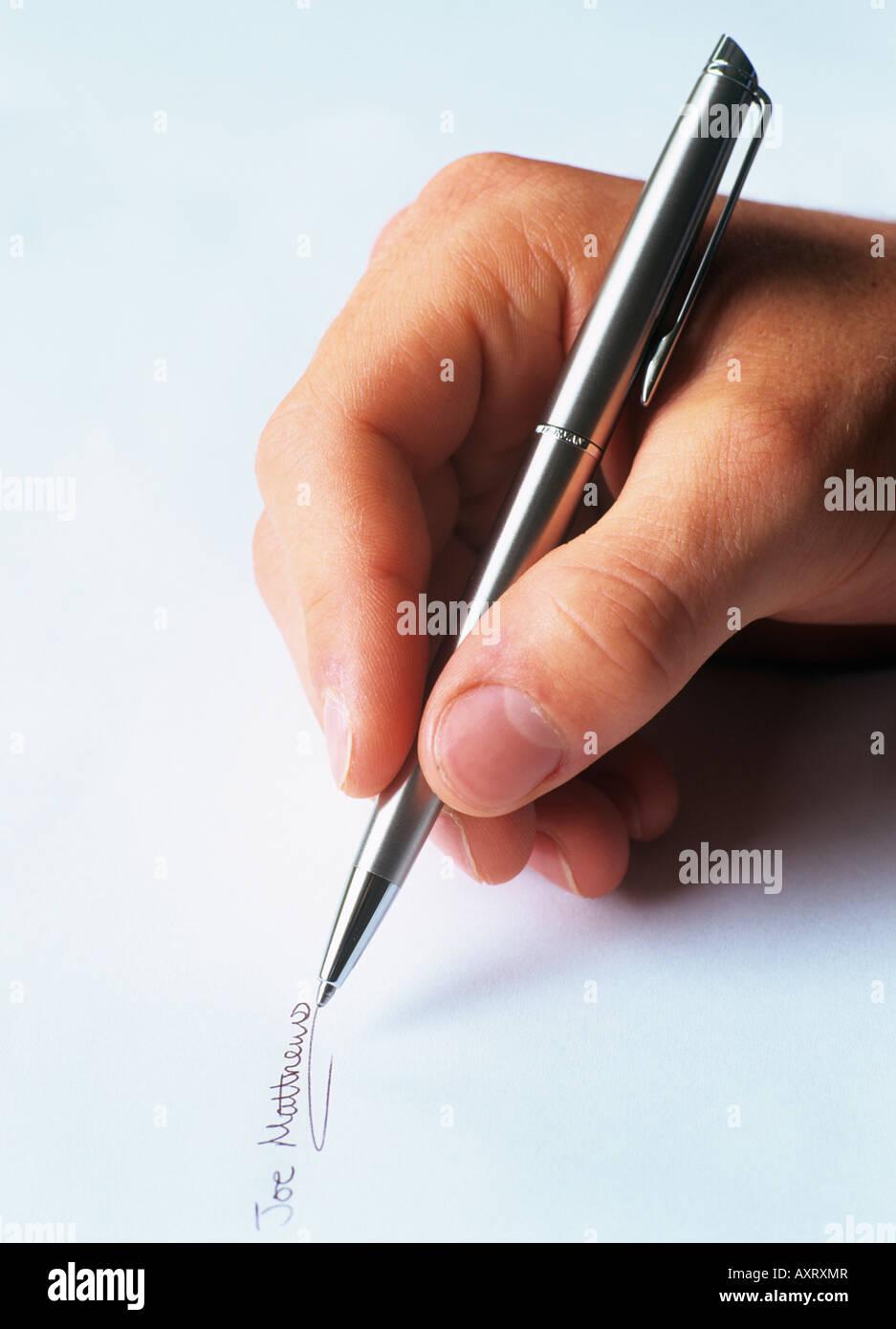 Des Menschen Hand schreiben eine Unterschrift auf Papier mit einem silbernen Kugelschreiber. England Großbritannien Stockbild