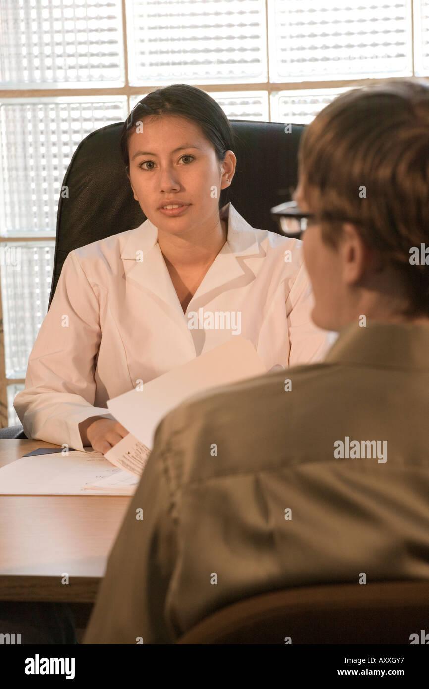 Ärztin spricht mit männlichen Patienten in ihrem Büro. Stockbild