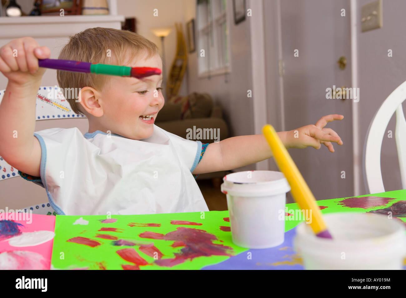 Zwei - jährigen Mädchen malen mit Farben Poster am Küchentisch ...