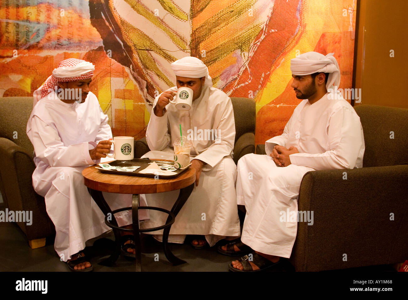 Junge arabische Männer mit traditioneller Kleidung sitzen im Starbucks Café in Deira City Center Einkaufszentrum Dubai Vereinigte Arabische Emirate Stockbild