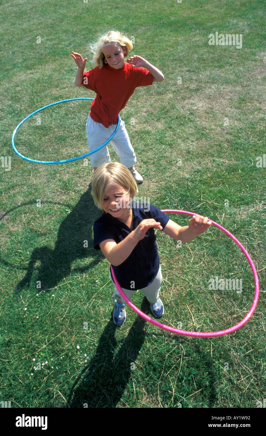 Zwei blonde Mädchen bewegt sich mit einem Hula Hoop Reifen Stockbild