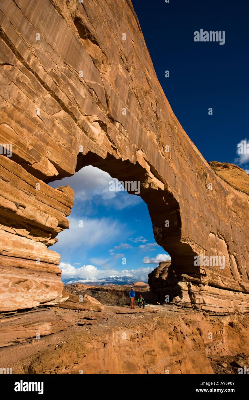 zwei Wanderer stehen unter Jeep Bogen in der Nähe von Moab Utah Stockfoto