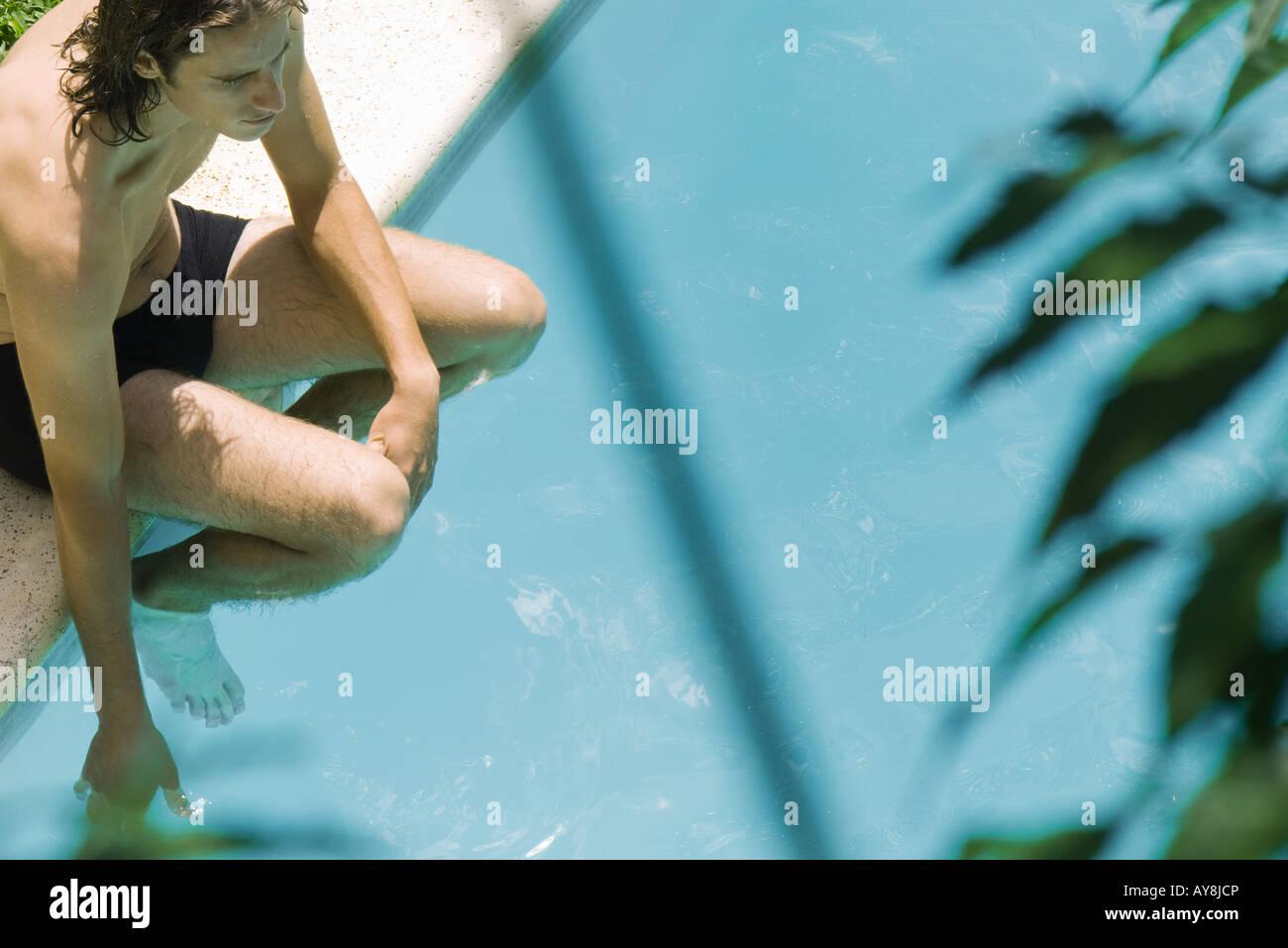 Mann sitzt neben Schwimmbad, einweichen, Füße und eine Hand im Wasser, erhöhte Ansicht Stockbild
