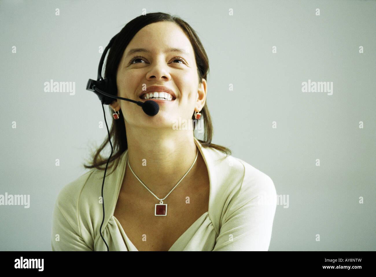 Frau trägt Kopfhörer, Kopf zurück, Lächeln, nachschlagen Stockbild