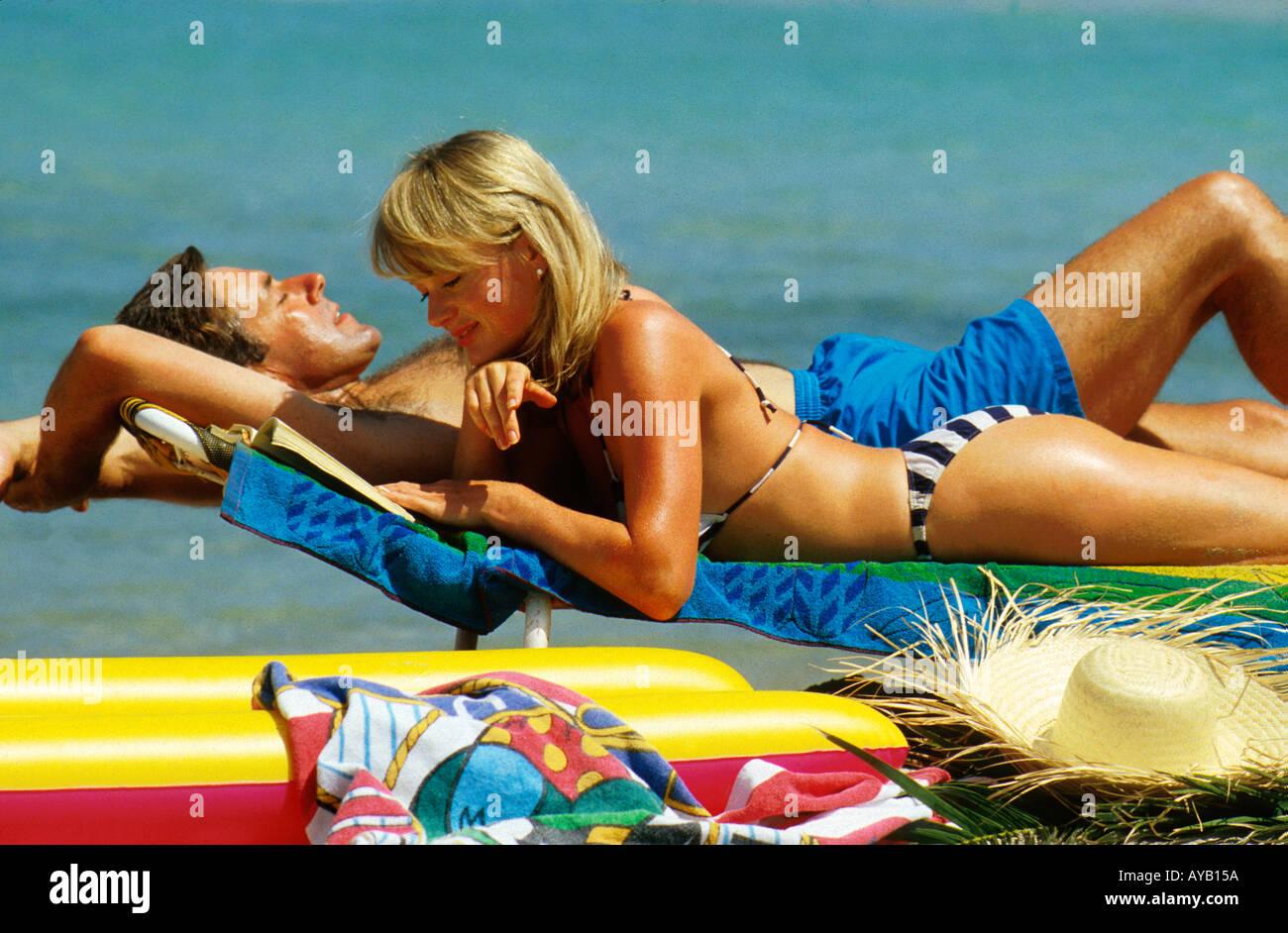 Paar entspannen auf den Sonnenliegen am Strand Stockbild
