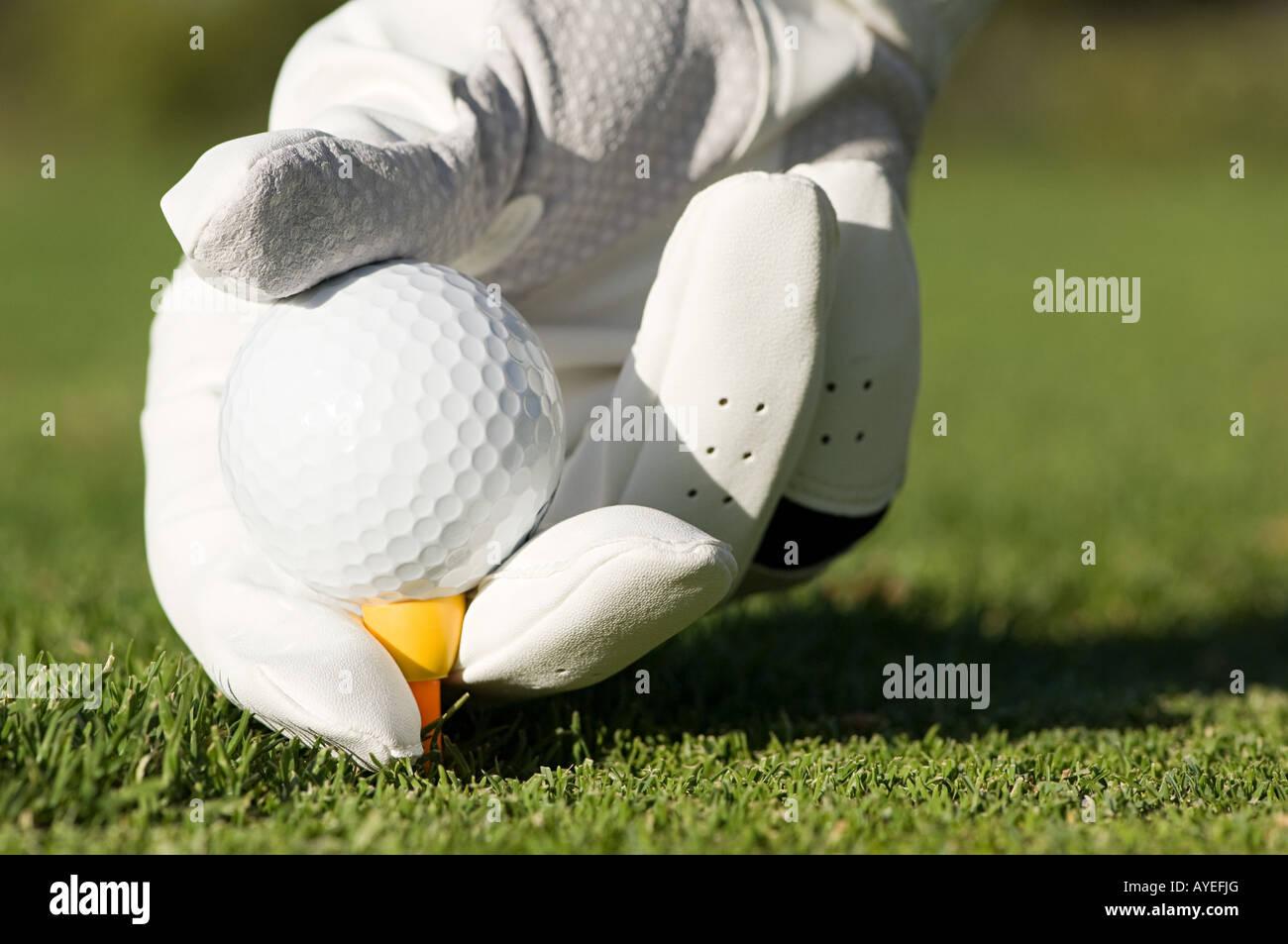 Eine Person, einen Golfball in ein t-Stück Stockfoto