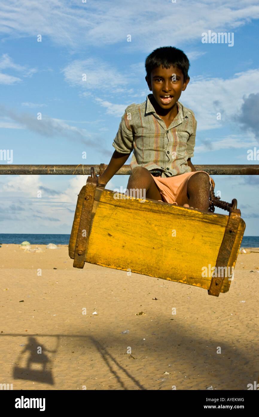 Indianerjunge auf einer Schaukel am Strand in Mamallapuram Südindien Stockbild