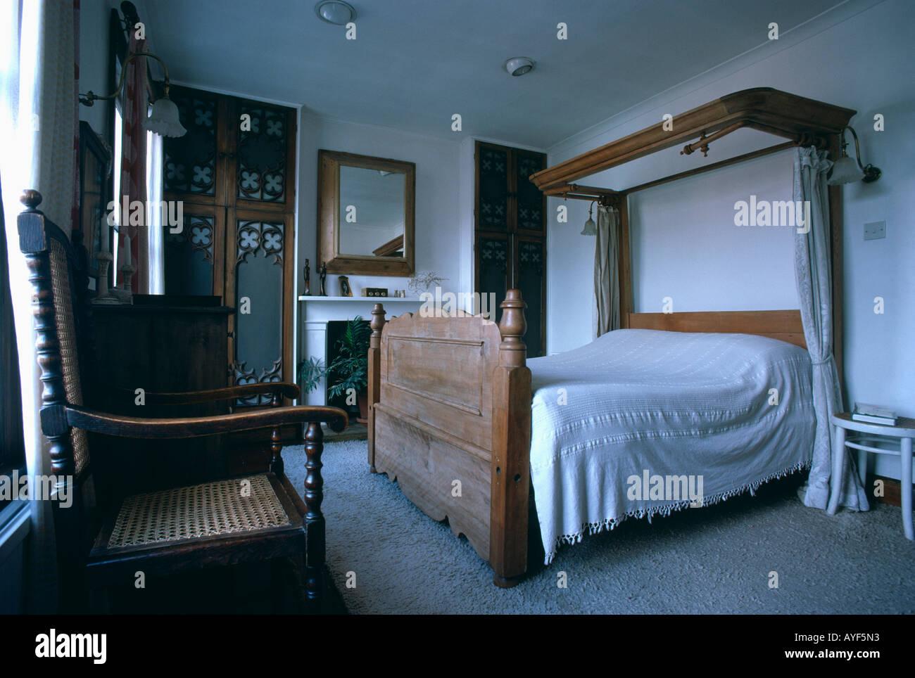 Weißes Schlafzimmer mit Bett und Antik Holzstuhl halbe tester ...