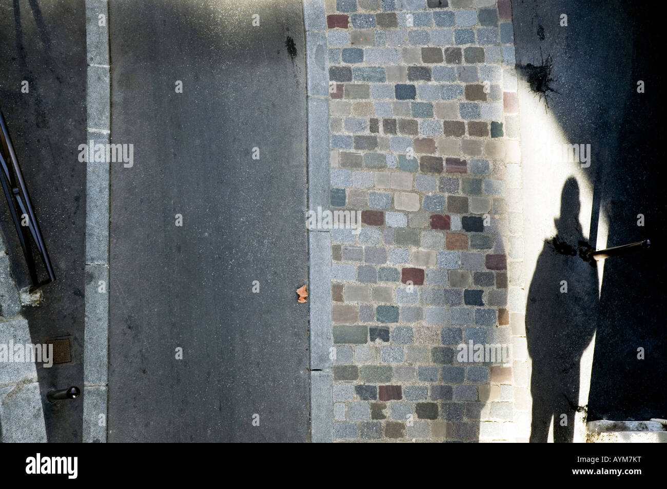 Schatten eines Mannes auf eine gepflasterte Straße mit düsteren Untertönen. Stockbild