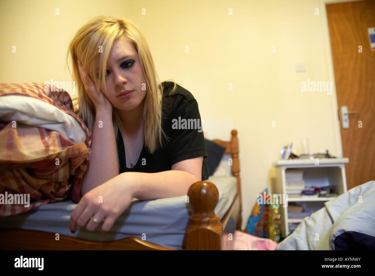 junge Teenager Frau weinend auf Bett liegend in chaotisch Ecktürme Schlafzimmer hielt ihren Kopf in einer hand Stockbild