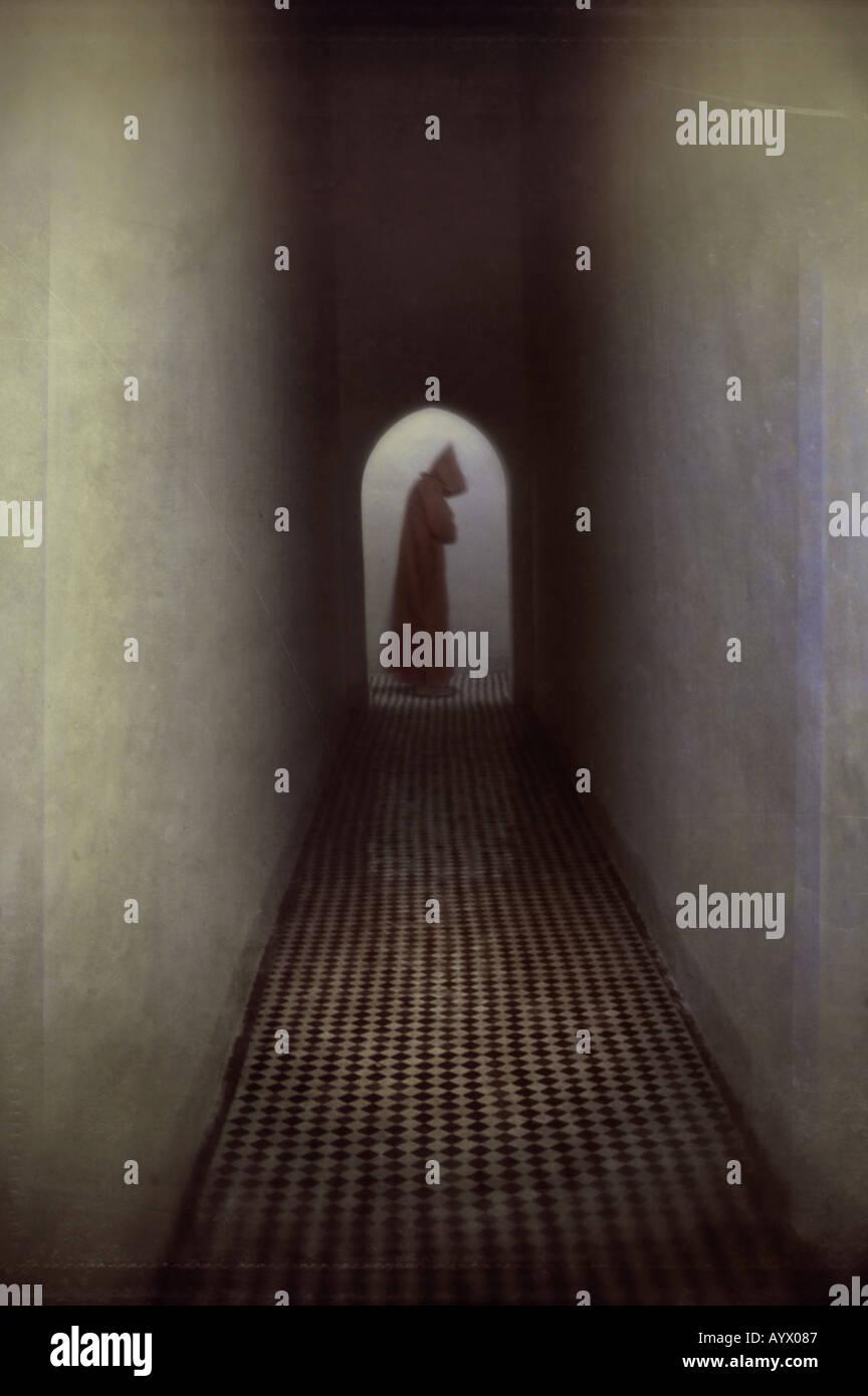 Mönch am Ende des Flures in gewölbte Tür Stockbild