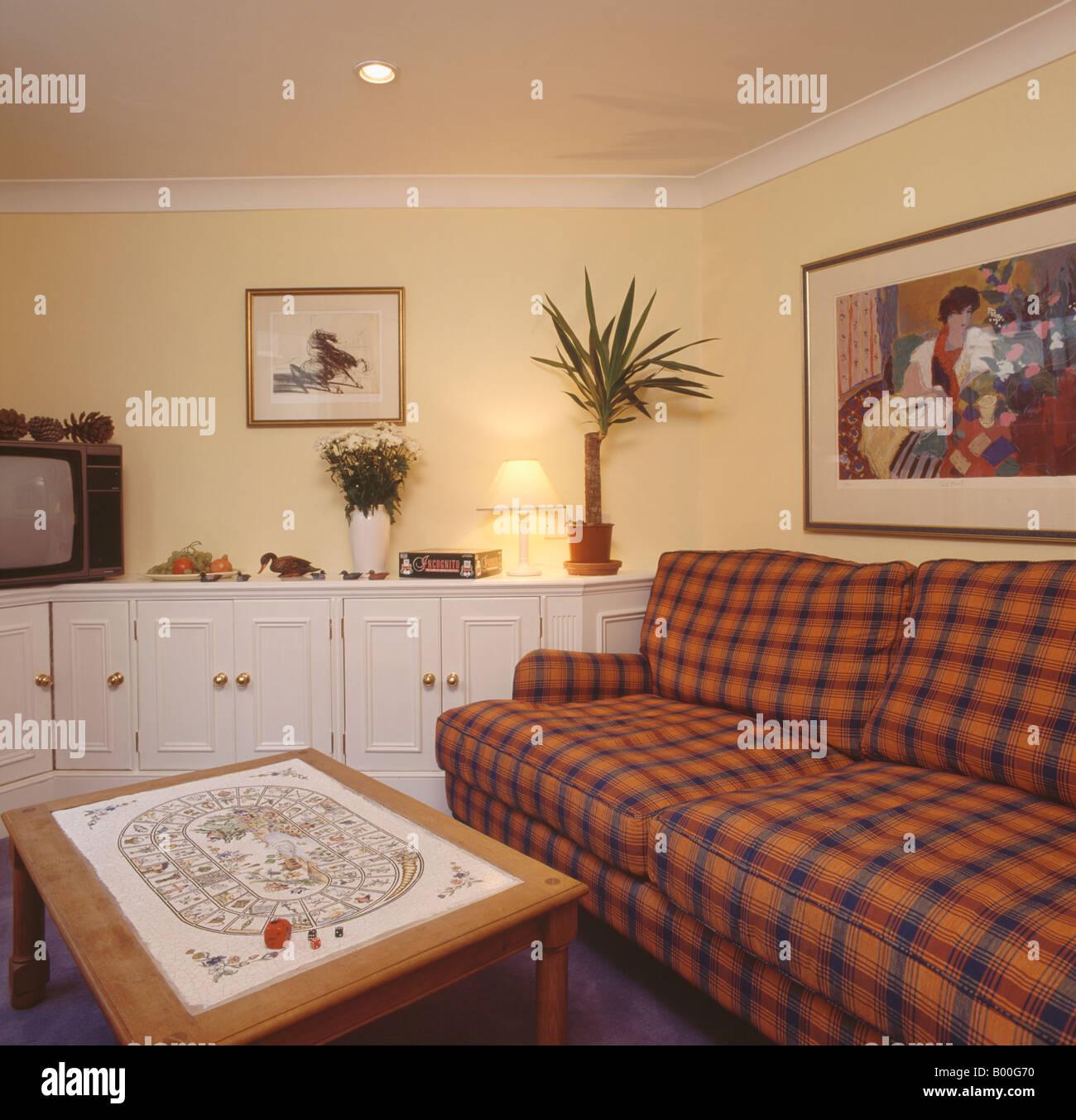 Orange und blau aufgegebenes Sofa in Pastell gelb Wohnzimmer mit ...