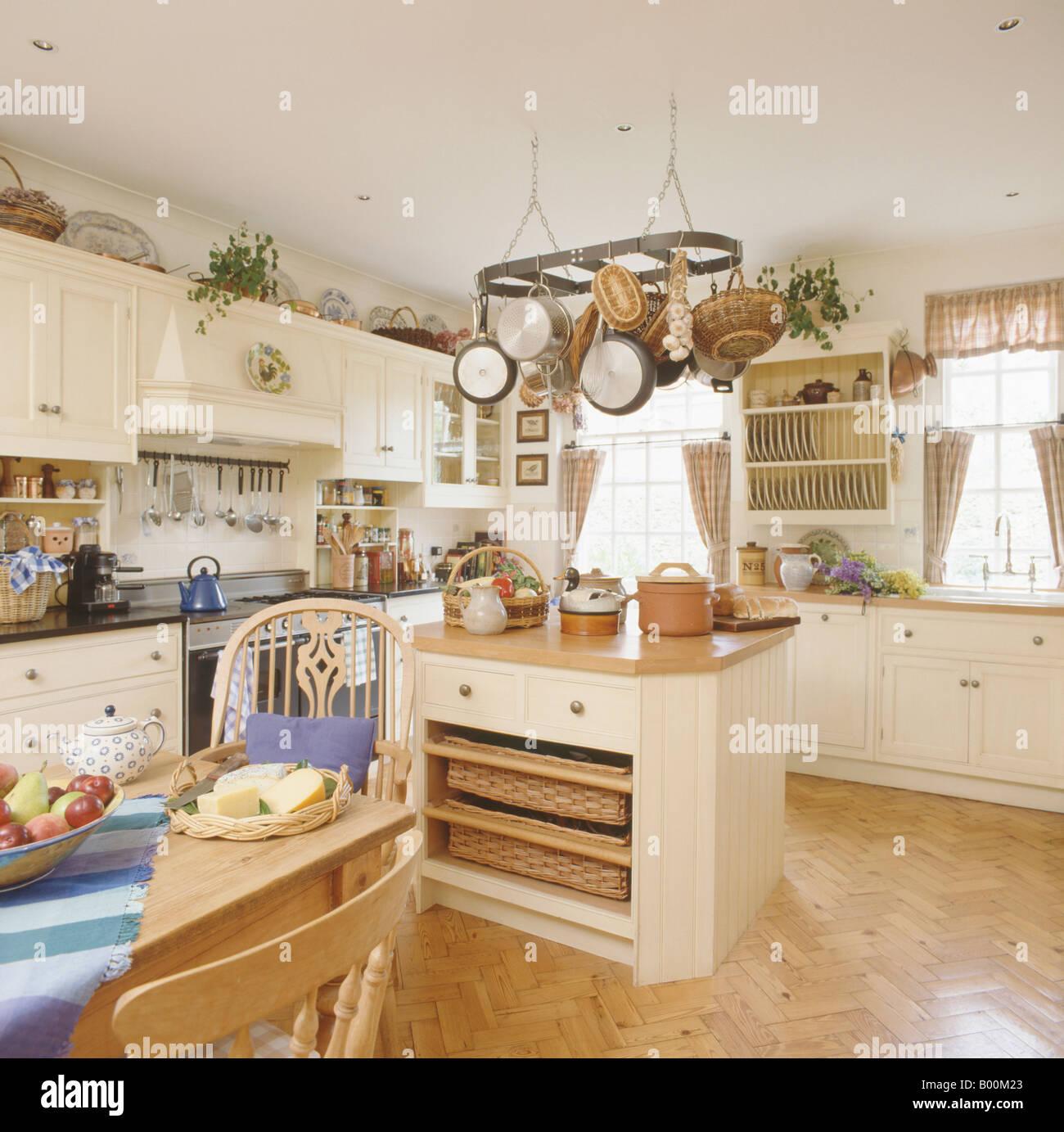 pfannen auf gestell oberhalb insel mit k rben lagerung auf regalen in creme k che mit parkett. Black Bedroom Furniture Sets. Home Design Ideas