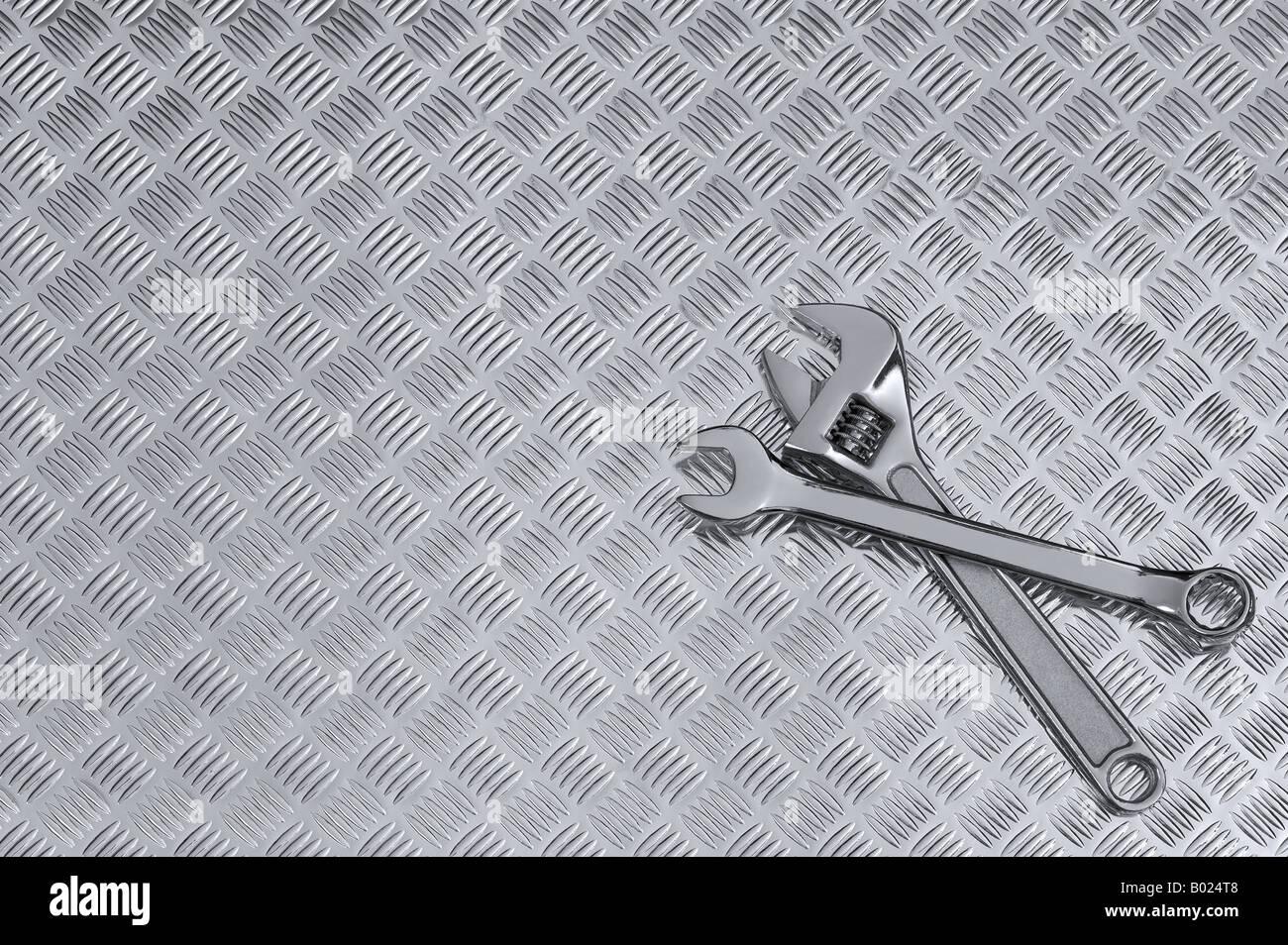 Mechanische Hintergrundbild von zwei Schraubenschlüssel auf einer Werkbank checkerplate Stockbild