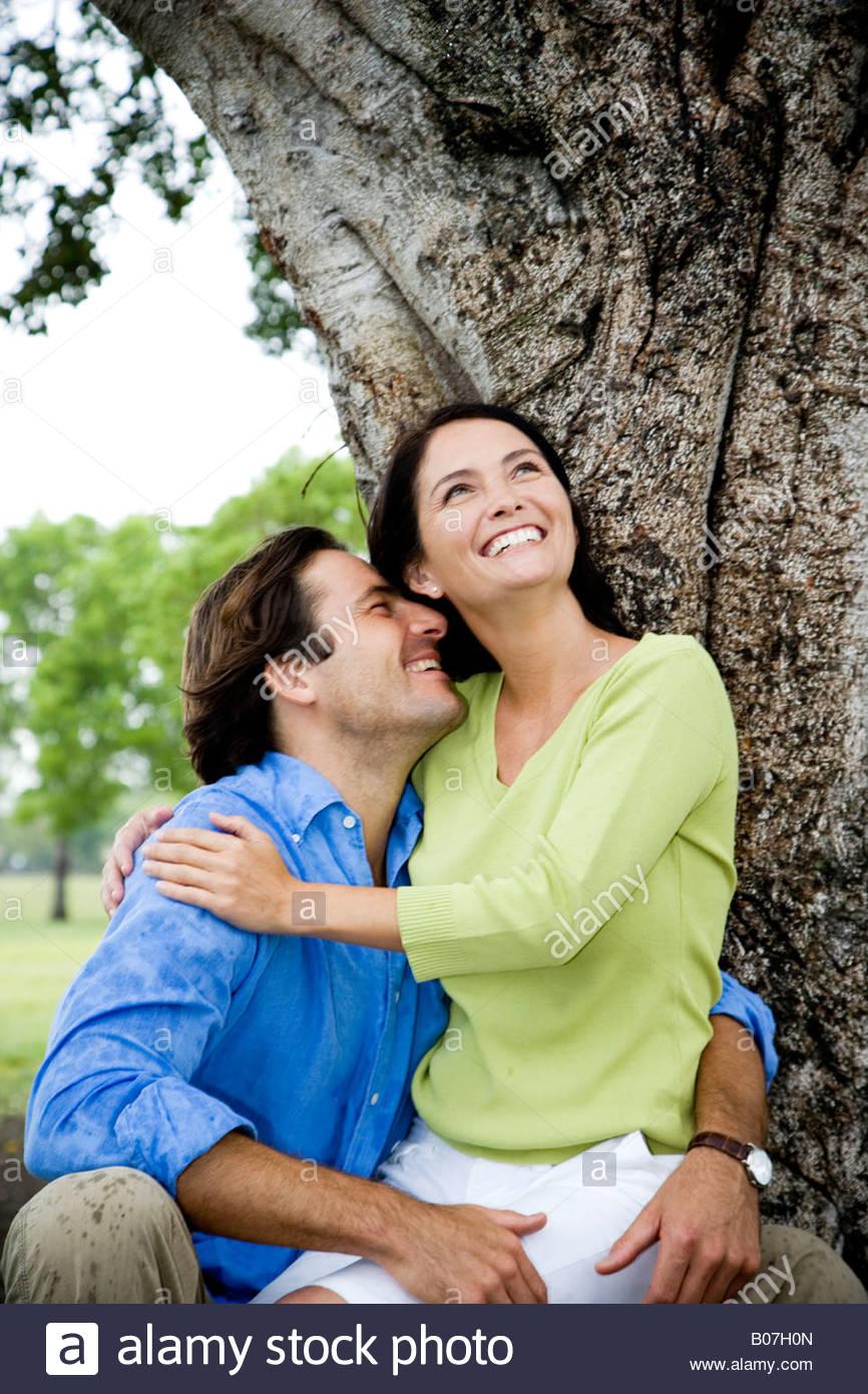 paar vor Baum umarmen Stockbild