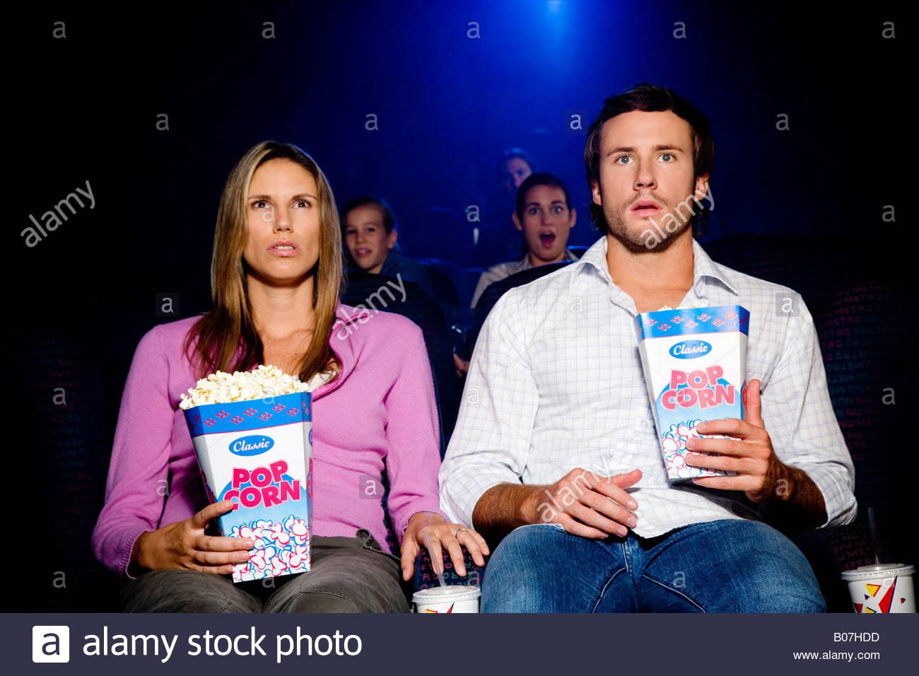 Paar im Kino einen schockierenden Film anschauen Stockbild