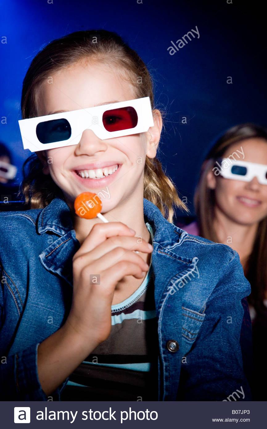 Mädchen mit Lollipop im Kino einen Film durch 3-d-Brille Stockbild