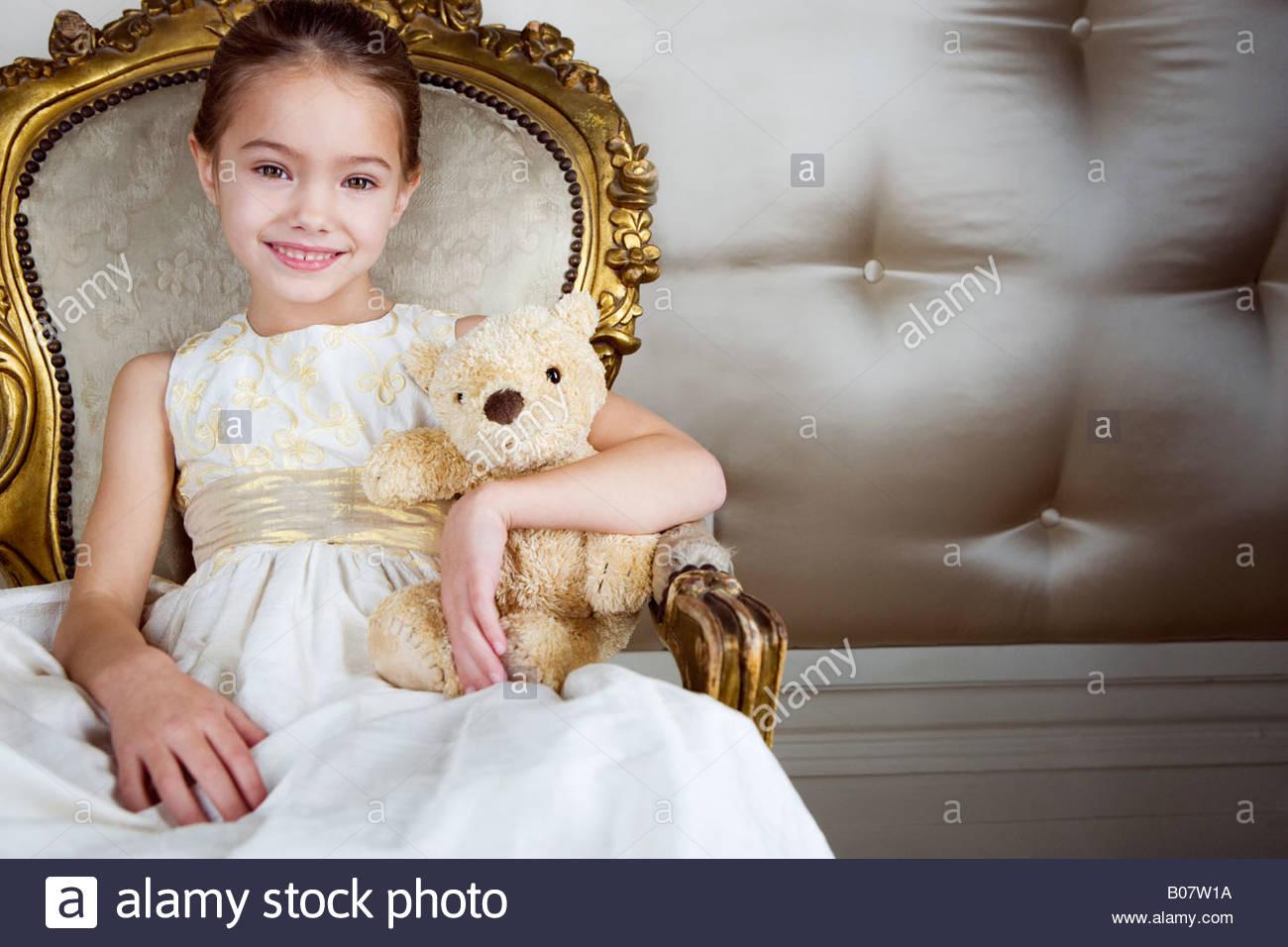 Kleines Mädchen sitzt in einem reich verzierten Stuhl trägt ein ...